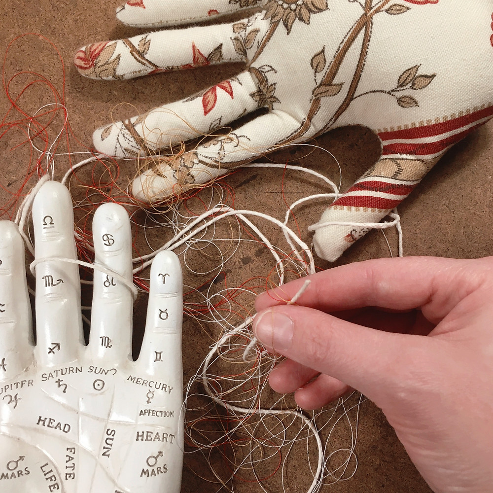 Photograph: a live hand lifts a strand of twine from a tangled jumble of threads and string, winding around a palmistry hand figurine and a stitched, vintage floral patterned, fabric hand.