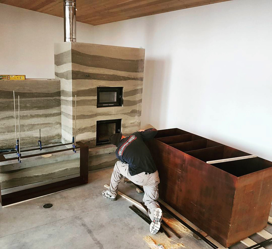 Rusted steel shelving being installed next to the site-built rammed earth masonry heater with it's heated reading bench.  image courtesy of McDiarmid Construction
