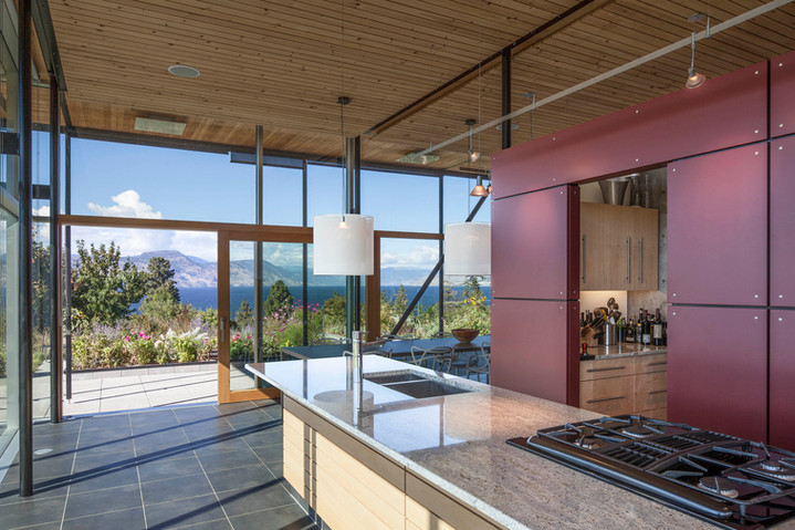 Interior view of the kitchen/dining/living pavilion with Okanagan Lake beyond.