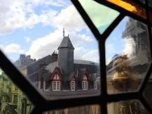 Toit d'un immeuble vu à travers un vitrail du Gros-Horloge