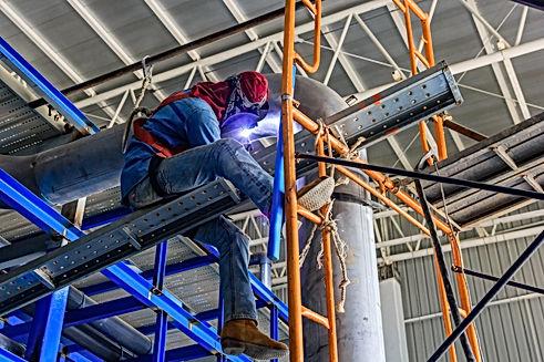 industrial-worker-with-protective-mask-welding-metal-piping-using-tig-welder.jpg