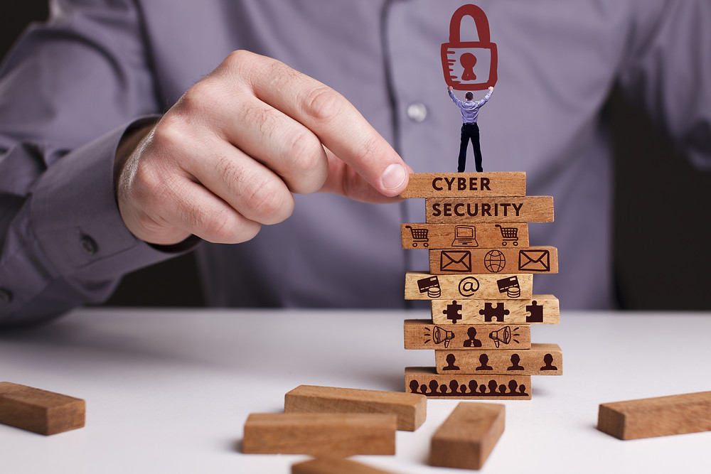 image of a man sitting at a table playing jenga stacked up with images of cyber security and puzzle pieces with a tiny man standing on top of the jenga puzzle holding up a lock to portray risk management