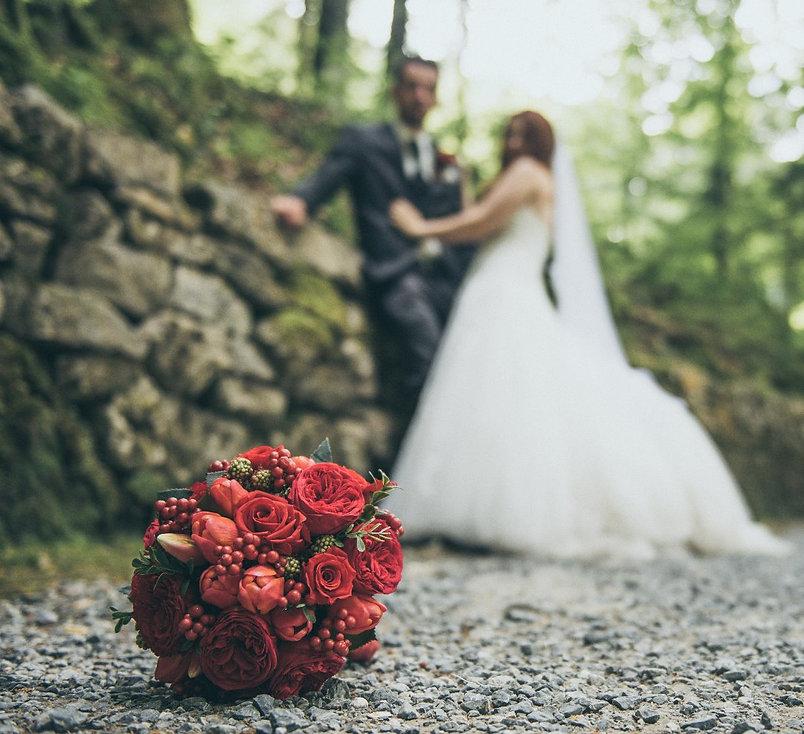 """Background Picture Brautstrauss24 Site """"Hochzeitspaar mit wunderschönem Brautstrauss im Vordergrund"""""""