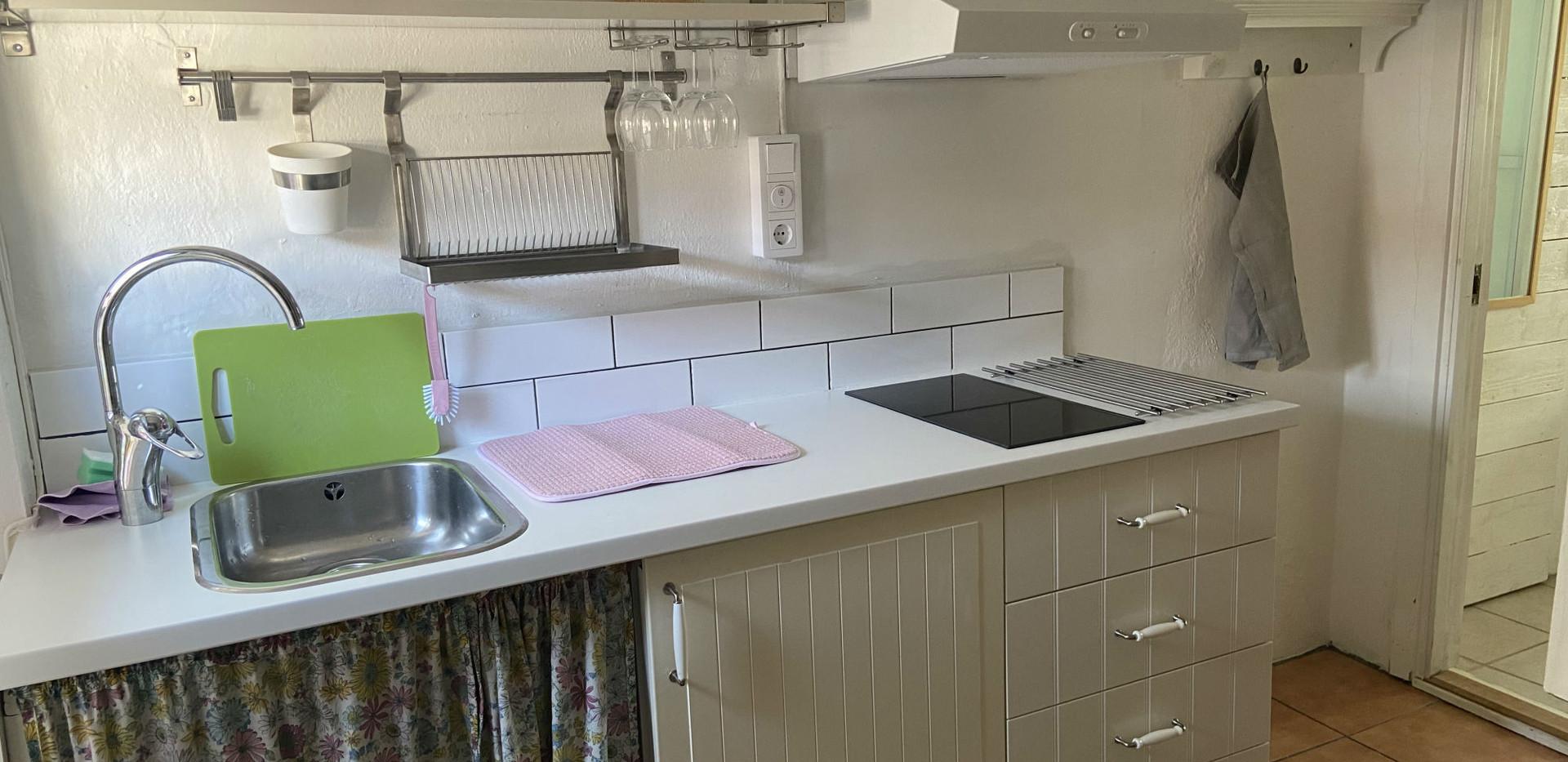 Grisstians lilla kök är utrustat med kylskåp, induktionsspis, mikrovågsugn och kaffekokare.