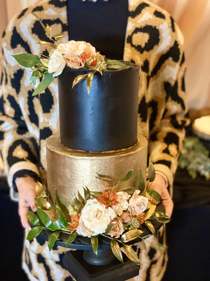 black and gold cake with flowers