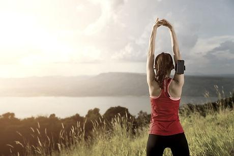 Sportlerin Rückenansicht dehnt ihre Schultern in der Natur.