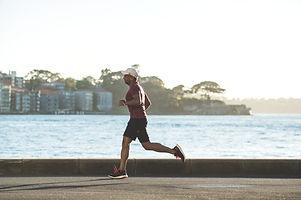 Leistungsstarker Sportler joggt am Wasser