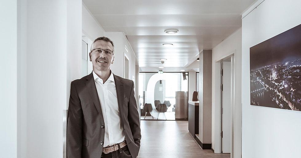 Präventionsmediziner Dr. Speer lehnt im Jacket an der Wand im Flur des OTC Regensburg