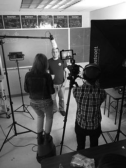 Three people stand in a studio filming an interview. Black and white.