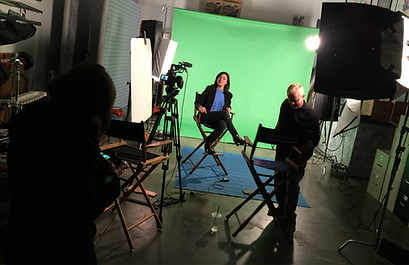 three people in a studio with a camera and green screen.