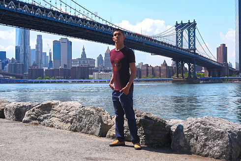Jacob is standing in front of Water street bridge in New York with a ProneToRide maroon shirt