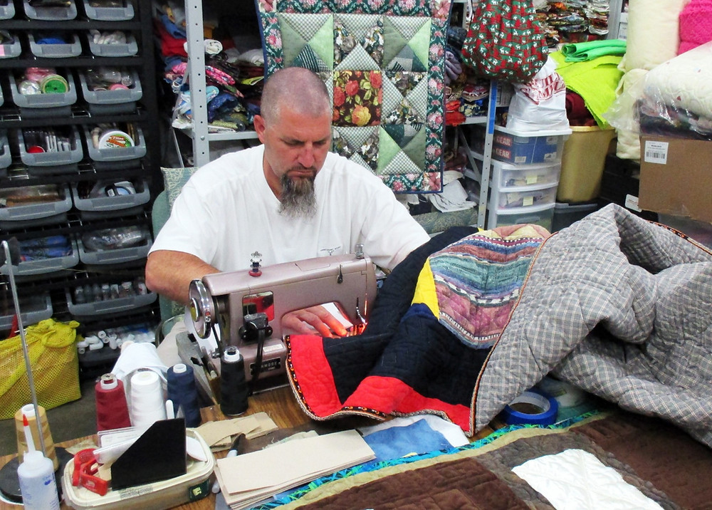 Inmate sewing quilt as part of restorative justice