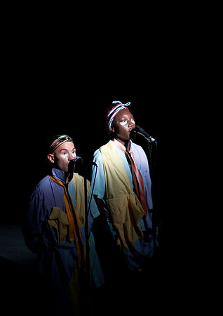 Two figures are lit with white light in the centre of a black background. One is a black, the other white. They are speaking into microphones on stands. They have matching makeup, red eyebrows and white semi-circles under their eyes. They are wearing loose light blue shirts with collars popped up and ties around their necks, they are also draped in pieces of yellow material.