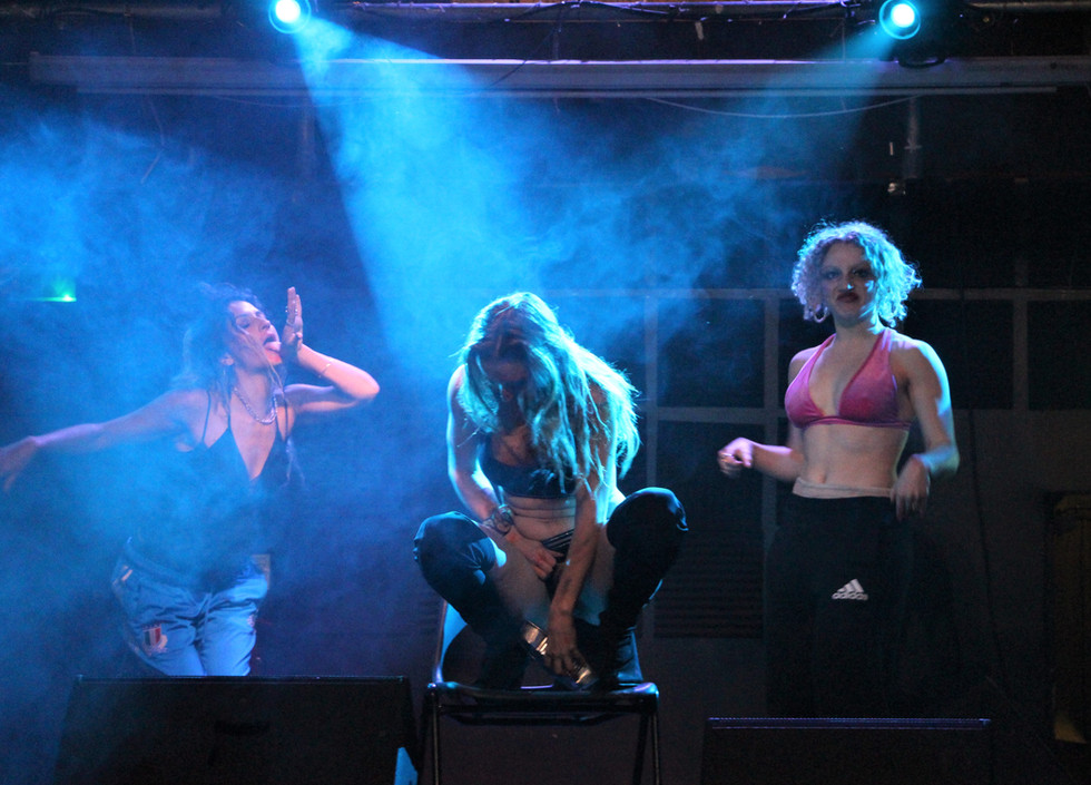 Lucy McCormick squats on  a chair, her falling hair obscuring her face. She is surrounded by two dancers.