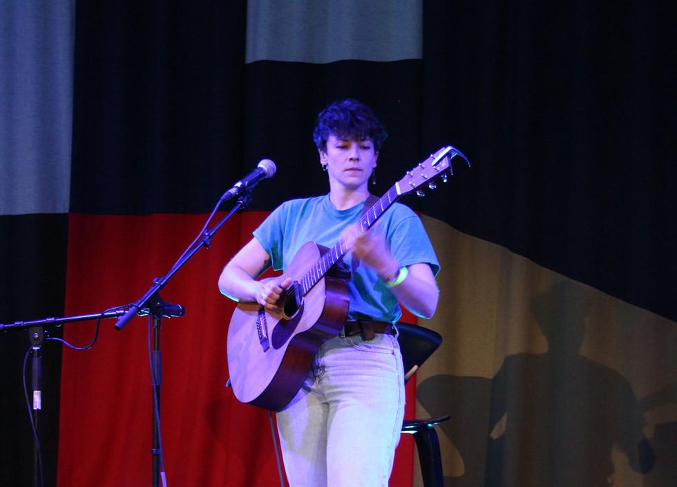 Rhiannon Scutt, a white woman wearing white jeans and a blue t-shirt plays a guitar