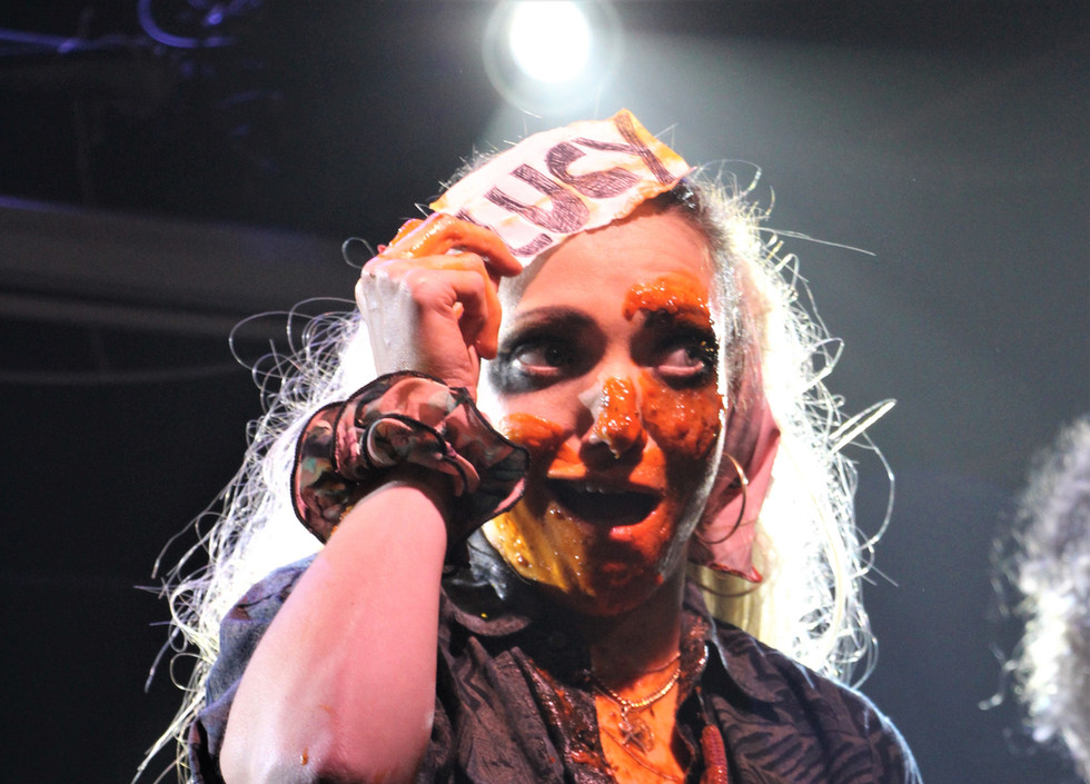 """Lucy McCormick holds a white piece of paper with """"Lucy"""" written on it to her forehead. Her face is covered in orange sauce. She is wearing a black shirt and multiple bumbags."""