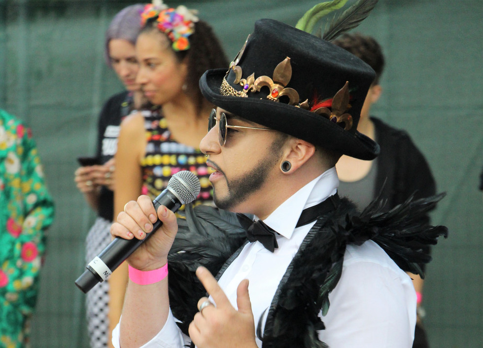 LoUis CYfer, a drag king wearing a black top hat decorated with a crown, white shirt and black tie, with feathered shoulders, speaks into a microphone.