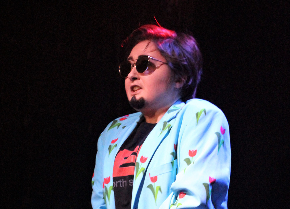 Indie, a drag king places his hands over his crotch. He is wearing matching blue jacket and trousers with a flower print, and a TED shirt.