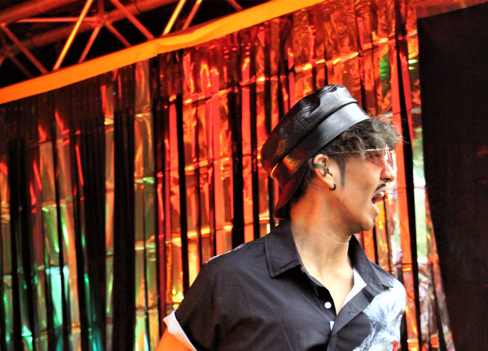 Chiyo, a drag king, wears a backwards black cap, black shirt, and trousers. His arms are stretched out behind him.