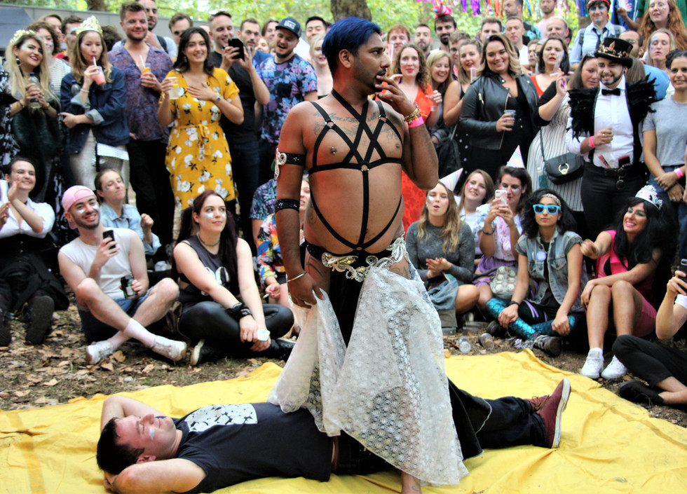 Snake Boy Sunny, a belly dancer, stands over a man lying down on a yellow sheet surrounded by the audience. Sunny, wearing a black harness and fabrics draped around his waist, holds one hand to his face as he surveys the audience, who are laughing.