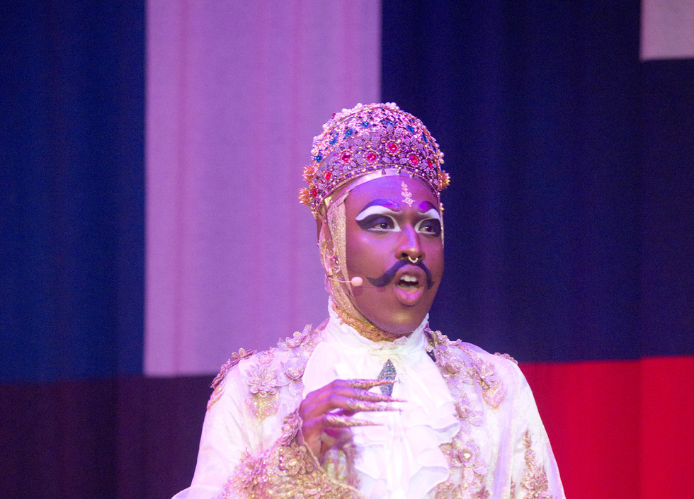 Rudy Jeevanjee, a brown man wearing an ornate outfit and golden crown, sings into a headset microphone.