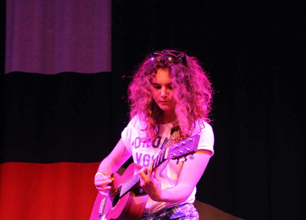 Chloe Hawes, a white musician wearing a white shirt, black jeans, and a flannel wrapped around their waist, plays the guitar