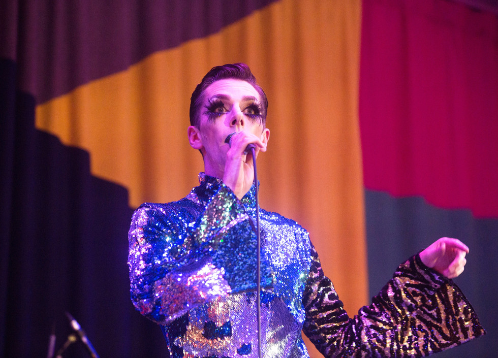 Bourgeois, a white man wearing pale stage makeup, long eyelashes, and a blue and tiger print glittery jumpsuit, stands onstage holding a microphone.
