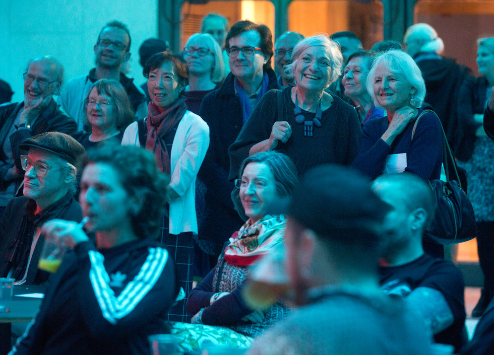 A crowd of audience members sitting and watching. They are bathed in a blue light.