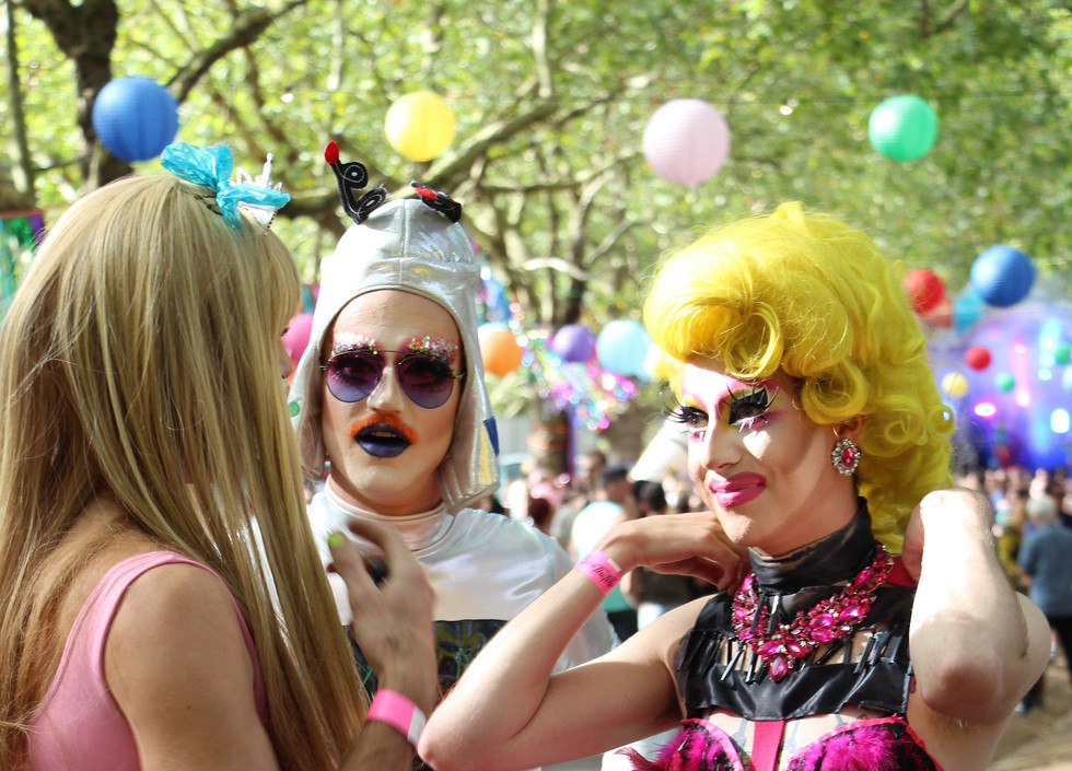Meth talks to a woman in a pink dress, while someone in a  silver bodysuit and helmet stands by.