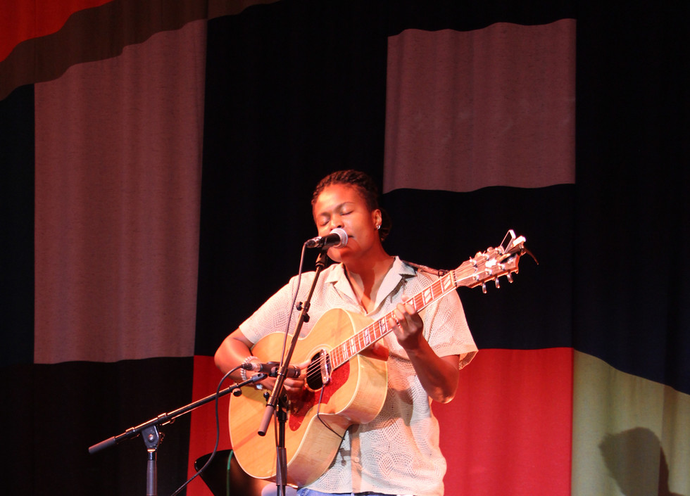 Sherika Sherard, a black woman wearing a white shirt and ripped blue jeans plays the guitar and sings
