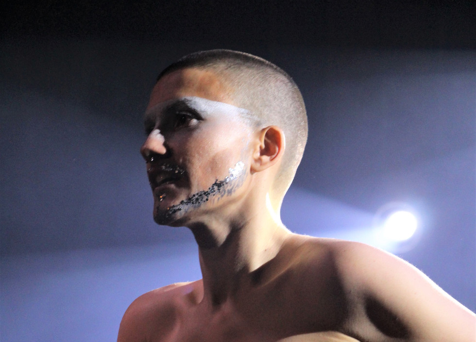 Silver, a drag king with a painted beard, faces the audience, topless.