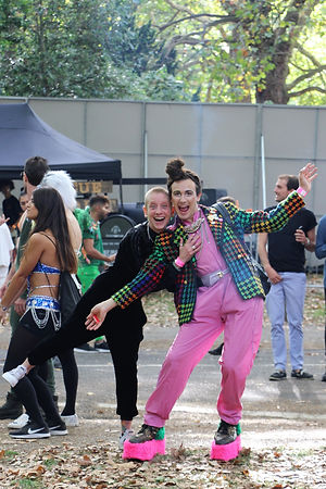 Two white people embrace in a pose for the camera. One has closely shaven hair and is wearing all back, they grip onto the back of the other person who has their arms outstretched and is wearing a bright pink jumpsuit and multicoloured jacket. Both are smiling for the camera. The backdrop is that of a festival in the summertime.