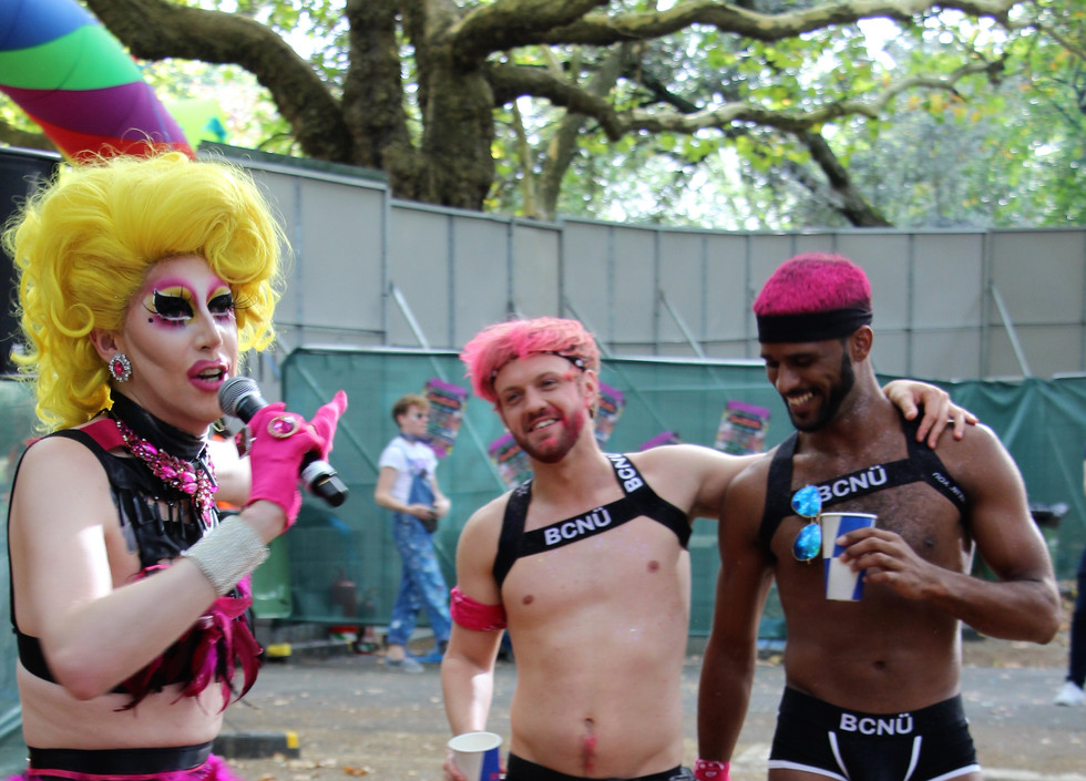 Meth, a white drag queen, speaks into a microphone as she gestures towards two men in matching black harnesses and underwear. Meth is wearing a yellow wig, and a pink and black two piece harness outfit.