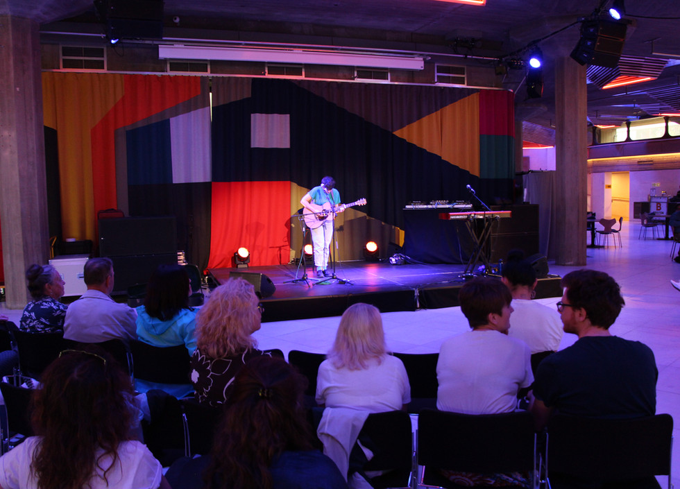 Rhiannon Scutt, a white woman wearing white jeans and a blue t-shirt plays a guitar and sings as the audience watches