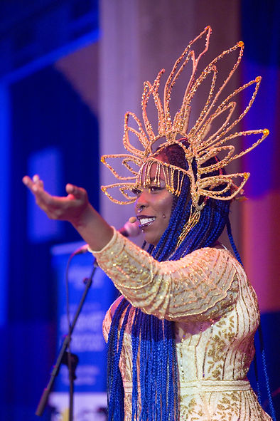 Saddie Sinner, a back woman, is smiling out to an audience, her hand is raised. She is wearing an ornate headdress that looks like a flower or sun. It is gold, studded with silver orange and gold jewels. She is also wearing a gold gown. Her hair is in long blue braids. The blue background features a microphone on a stand.