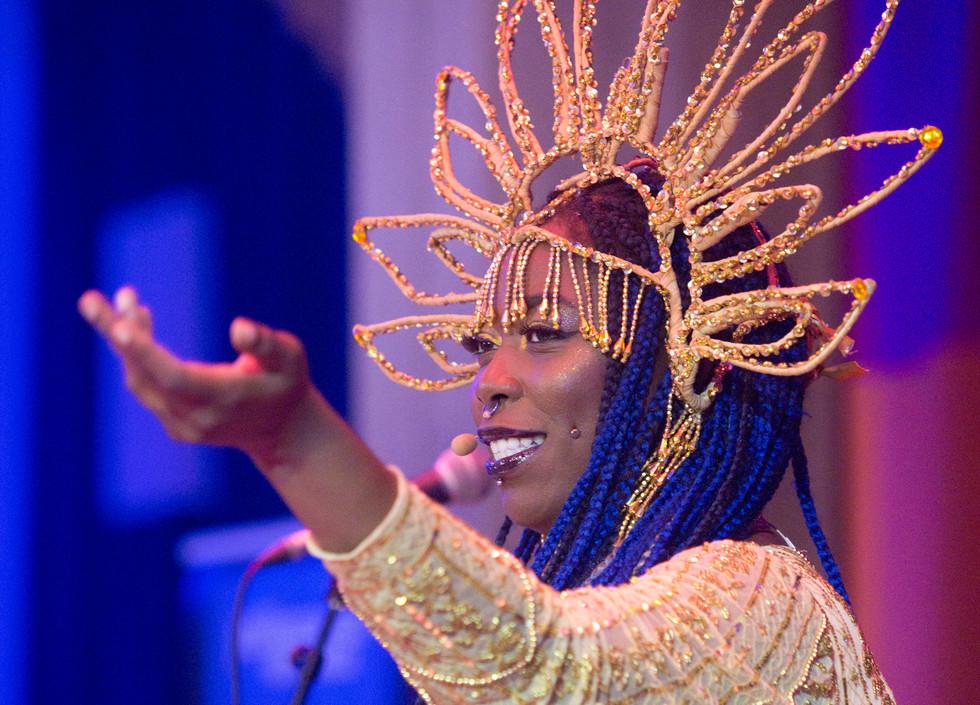 Sadie Sinner, a black woman, wearing a beaded dress and headpiece, raises her left arm upwards.