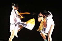 A black image with two very blurred figures. They appear to be dancing frantically. They appear as two blurs of yellow, light blue and white. The figure on the right is bent over, their bare legs are visible. The figure on the left is stood up straight, also bare legged with one knee raised.