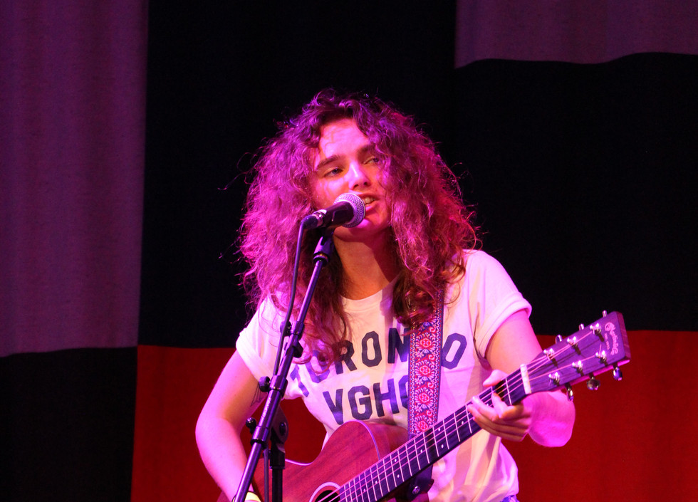 Chloe Hawes, a white musician wearing a white shirt, black jeans, and a flannel wrapped around their waist, plays the guitar and sings