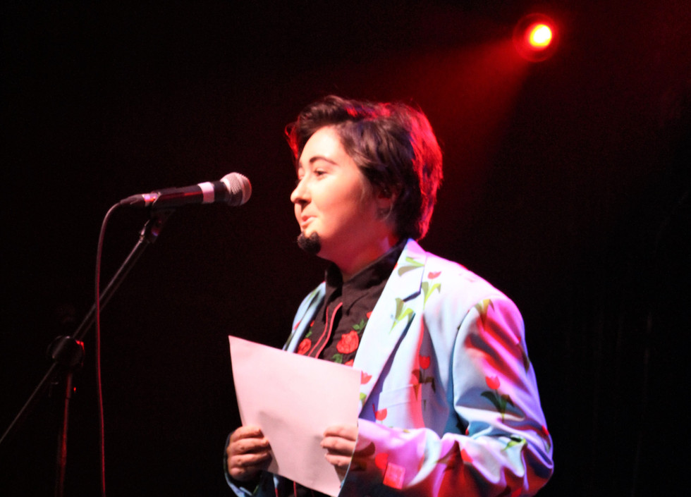 Indie, a drag king, holds a piece of paper and stands in front of a microphone. He is wearing matching blue jacket and trousers with a flower print, and a TED shirt.