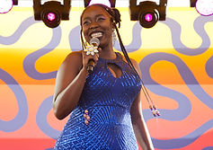 Saddie Sinner, a black woman, stands in front of a pink and purple patterned background. She is holding a microphone and smiling warmly. She is wearing a sparkly fitted halter neck blue dress. Her braided hair is worn up, with a few long braids loose on each side.