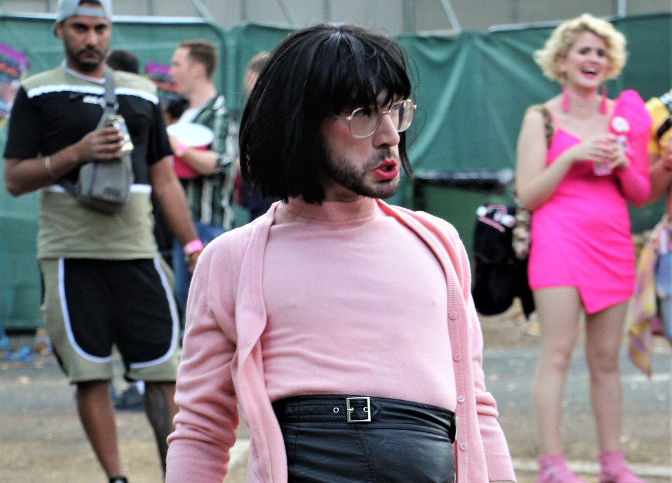 Harry Clayton-Wright, a queer performer, wears a black bobbed wig, pink top and cardigan, and black skirt and stockings. They are also wearing pink rubber gloves, and in their right hand they are holding a feather duster.