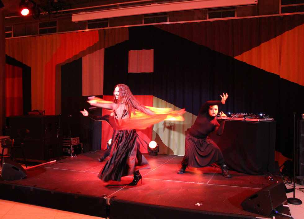 Le Fil, a British-Chinese man twirls onstage in a black dress with red fabric, accompanied by two dancers dressed all in black