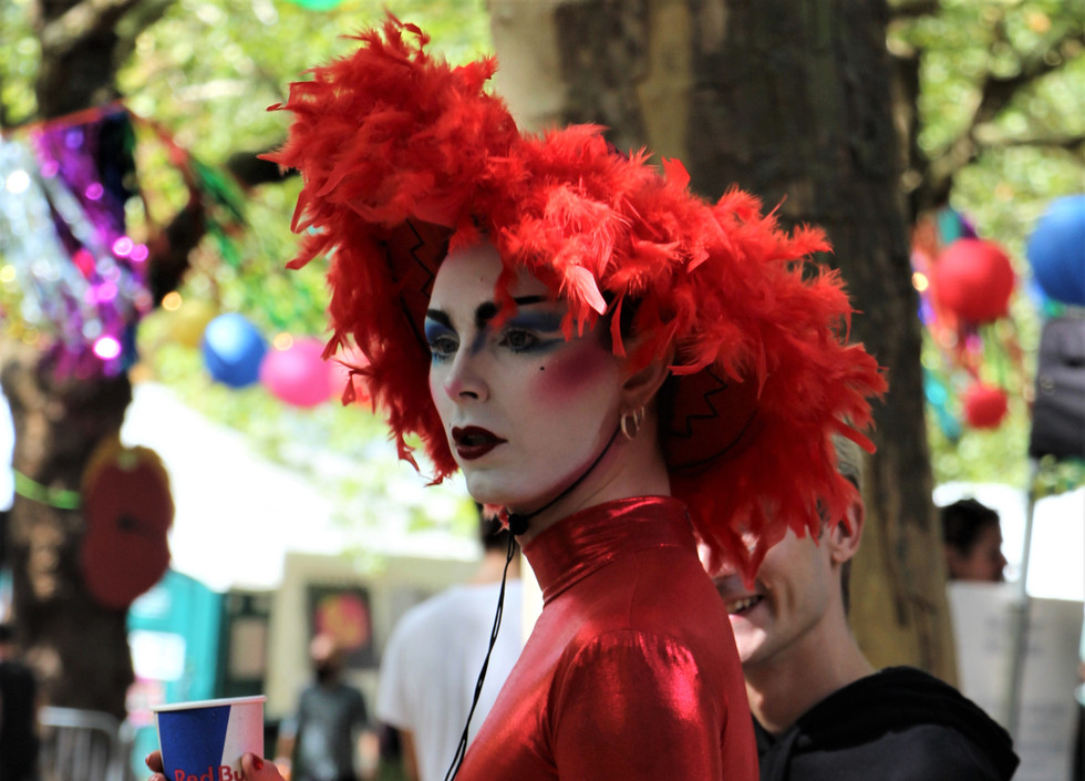 Finn, a white drag performer, wearing a red bodysuit with a matching red feathered hat.