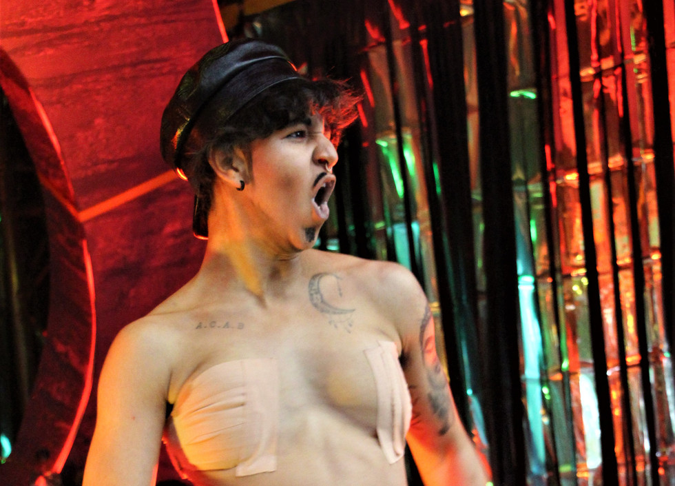 Chiyo stands with all his clothes off, revealing his bound chest. Aside from his hat, the only other piece of clothing he has on is a black piece of underwear to which is attached a rainbow strap-on dildo, which Chiyo grabs in one hand.