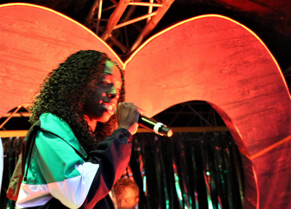 Karnage, a black woman, performs into the microphone. She's wearing a green, white, and black striped jacket.