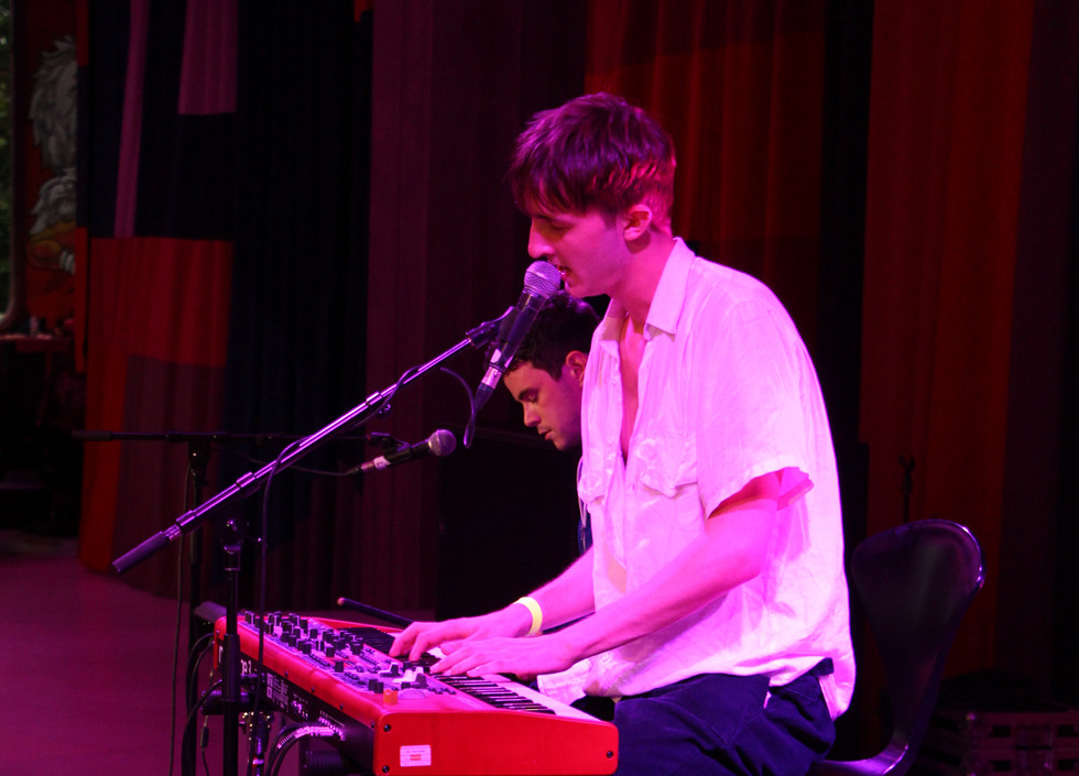 Vaughan Music, a white man in a white shirt plays the keyboard and sings