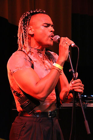 A black man sings intensely into a microphone. He has shoulder length bcal and blond braids. He is of muscular build. He is wearing a tight shirt, black braces and a gold bangle with a yellow paper wristband. The whole image is basked in a reddish, orange light.