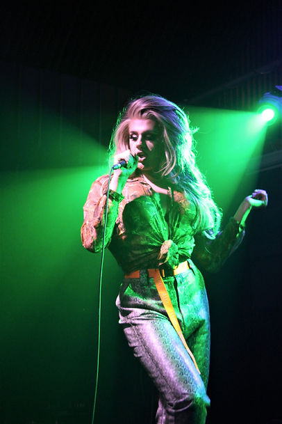Ophelia, a drag queen sings into a microphone. She wears a snake skin effect shirt, tied at the waist and snakeskin trousers with a yellow belt. She has long, blond-white hair. She stands on stage, with green light behind her.