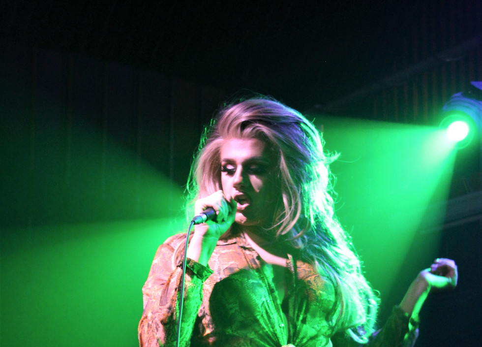 Ophelia, a drag queen, wearing snakeskin patterned trousers and shirt, sings into a microphone.