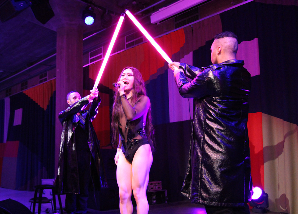 Le Fil, a British-Chinese man wearing a black bodysuit sings as two dancers wearing black trench coats hold two glowing light sticks over his head in a triangular formation